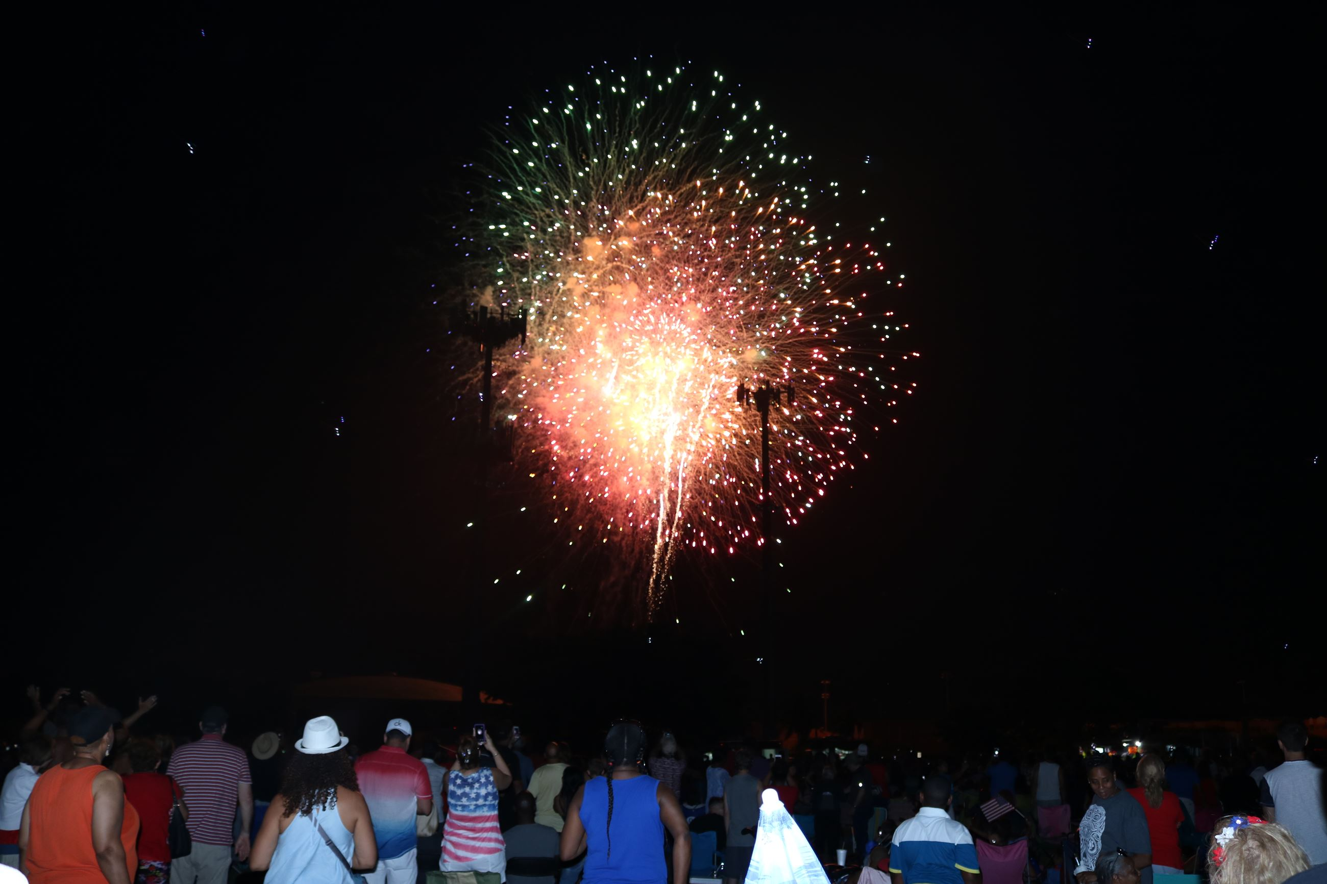Crowd enjoys the fireworks display at July 4th event.